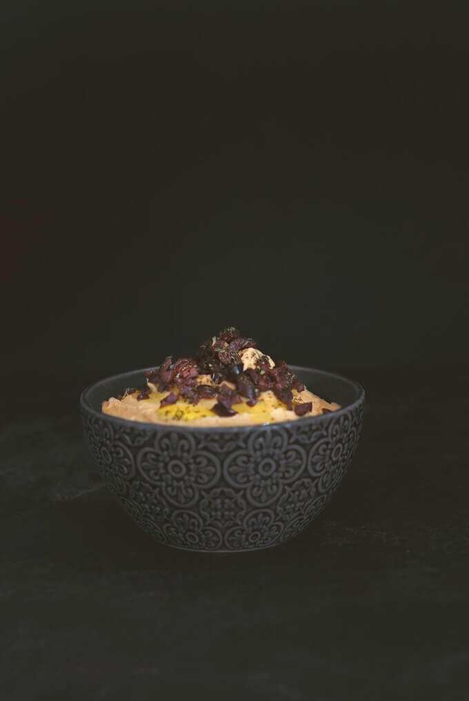 A black bowl full of pumpkin hummus garnished with black olives and olive oil by FamilySpice.com