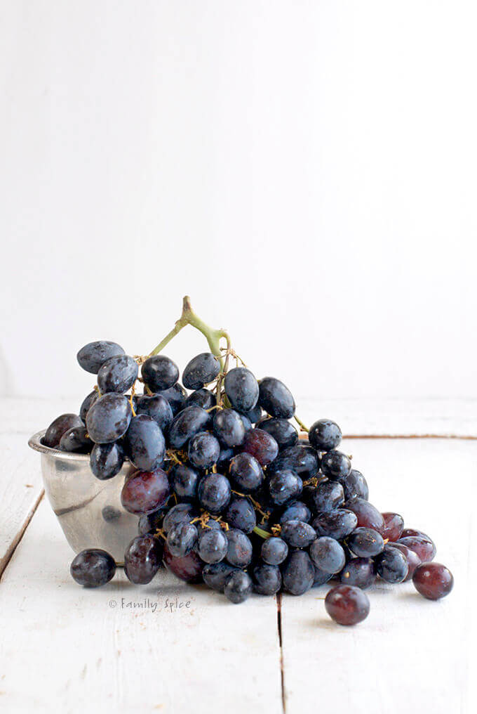 A large bunch of black grapes in a metal bowl by FamilySpice.com