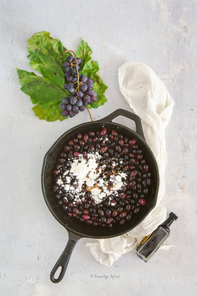 A cast iron skillet with grapes topped with cornstarch in it and fresh grapes next to it