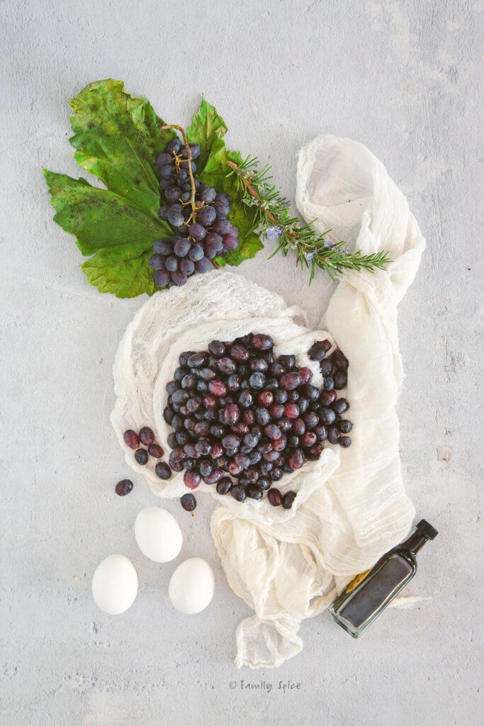 Grapes washed and stemmed on a cheese cloth with eggs, a bunch of grapes and small bottle of balsamic vinegar next to it