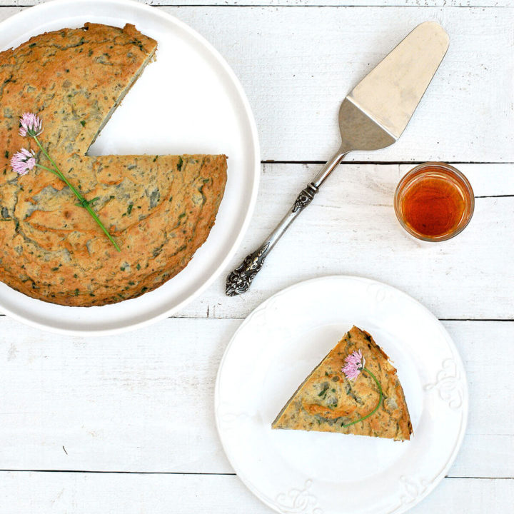 Overhead view of Persian Mashed Potato Quiche with herbs on a serving plate with a piece cut out (Kookooyeh Sib Zamini)