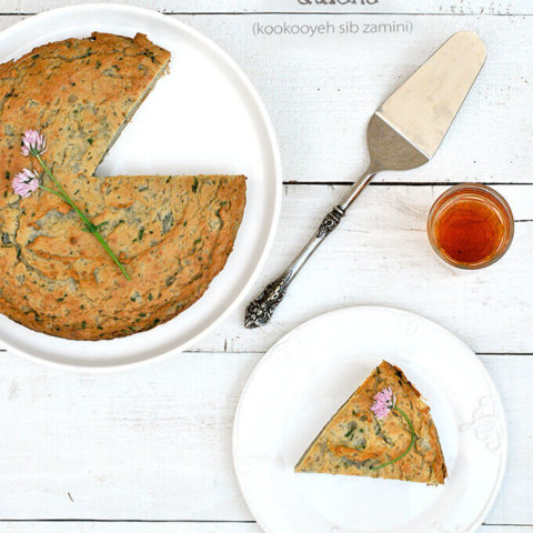 Overhead view of Persian Mashed Potato Quiche with herbs on a serving plate with a piece cut out (Kookooyeh Sib Zamini) by FamilySpice.com