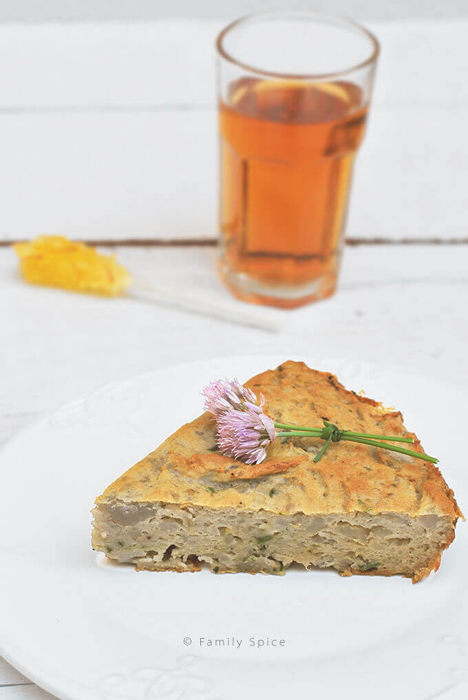 Close up view of a slice of Persian Mashed Potato Quiche with herbs on a serving plate with a cup of tea (Kookooyeh Sib Zamini) by FamilySpice.com