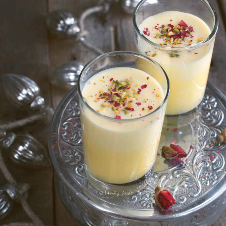Two glasses of saffron eggnog garnished with rose petals and pistachios