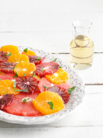 A citrus salad made with grapefruit, oranges and blood oranges on a platter with a small bottle of mint shrub