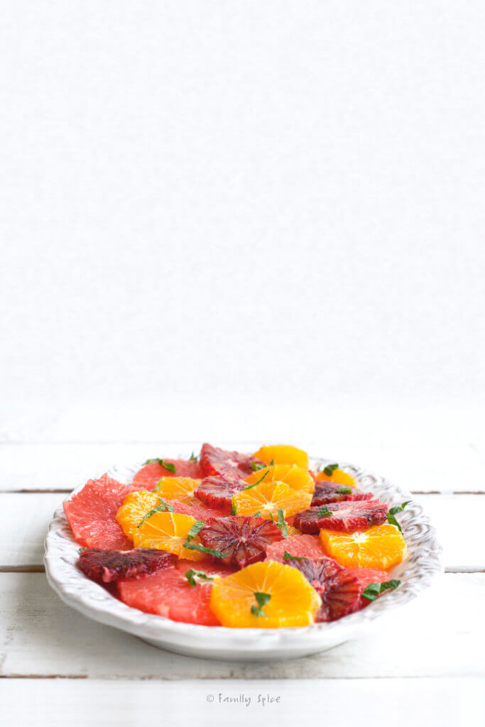 A citrus salad made with grapefruit, oranges and blood oranges on a platter garnished with fresh mint