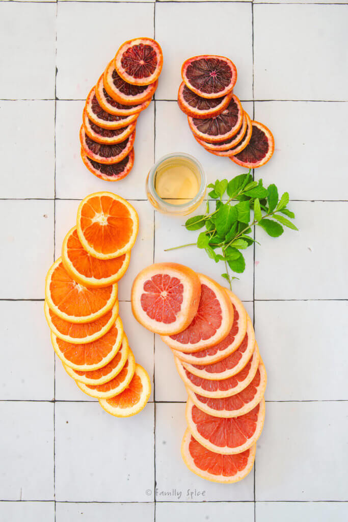 Round slices of oranges, grapefruit and blood oranges with fresh mint and a small bottle of mint shrub
