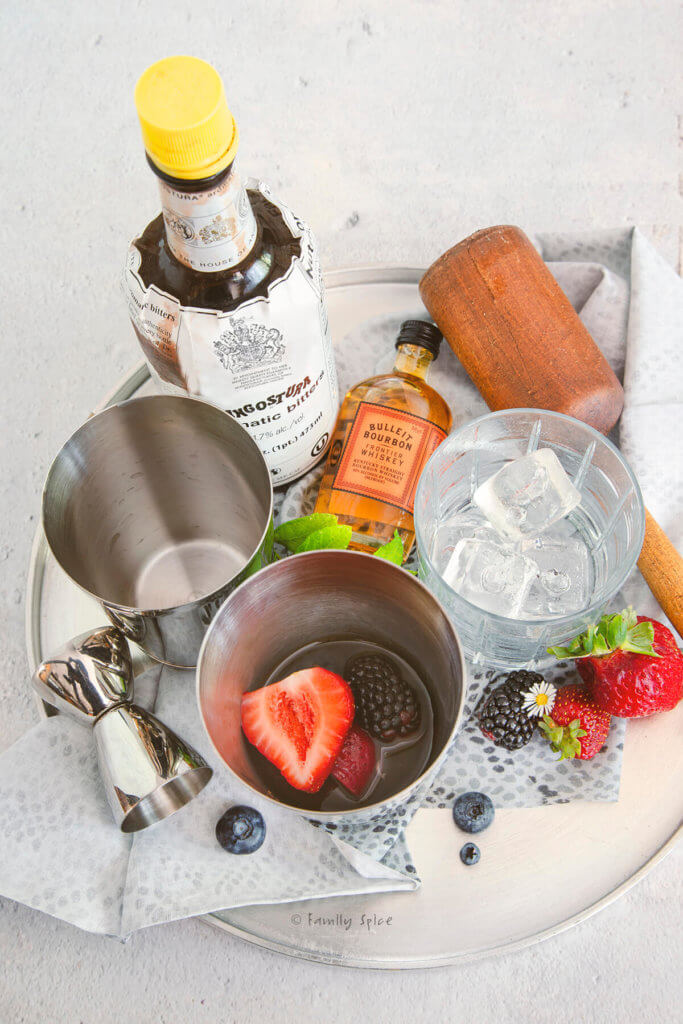 A metal tray with a shaker mixer filled with fruit and alcohol along with a glass with ice, bottles of bourbon and bitters and a muddler
