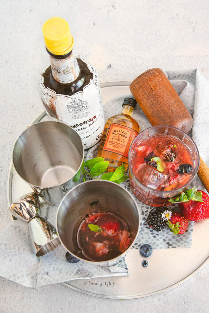 A metal tray with a shaker mixer filled with berry bourbon smash along with a glass with ice and cocktail, bottles of bourbon and bitters and a muddler