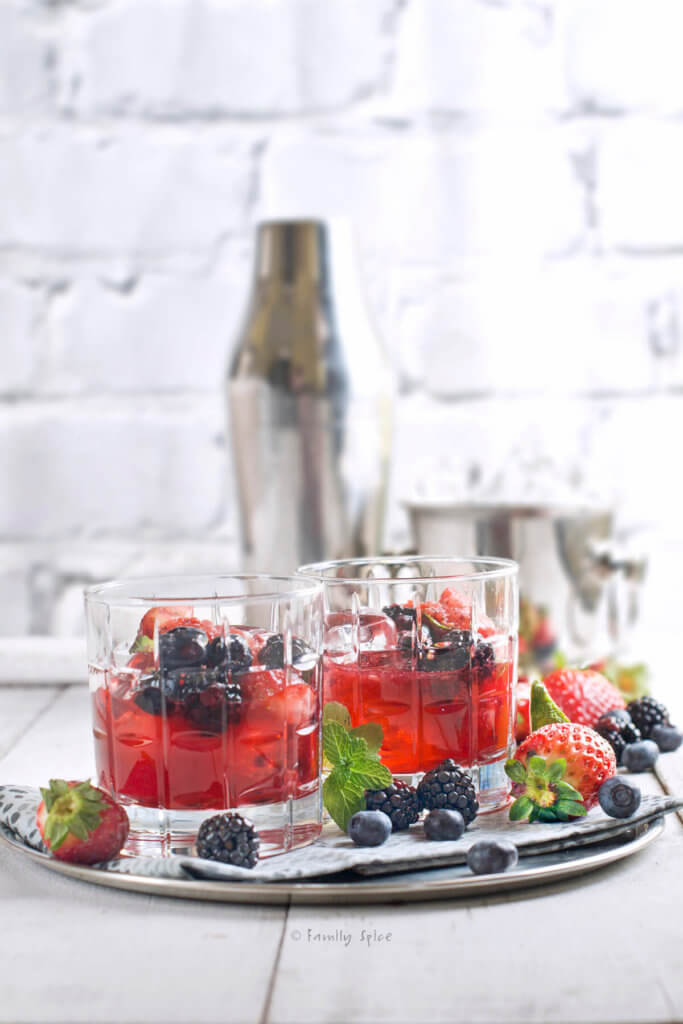 Side view of a metal tray with two glasses filled with berry bourbon smash and a cocktail shaker behind it