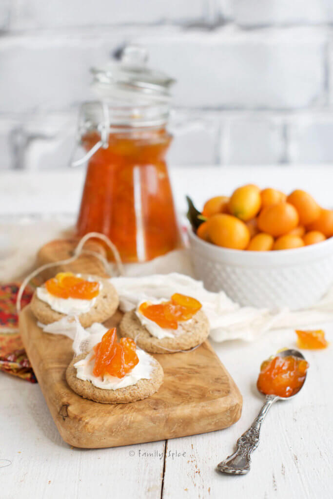 Side view of a cutting board with crackers topped with cheese and jam with bottle of kumquat jam and bowl of kumquats behind it