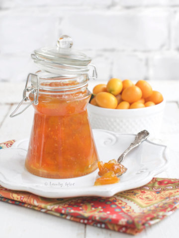 A triangular glass canning jar with kumquat marmalade in it with a bowl of kumquats behind it