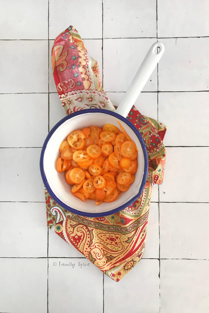 Slices of kumquat jam in a white enamel pot