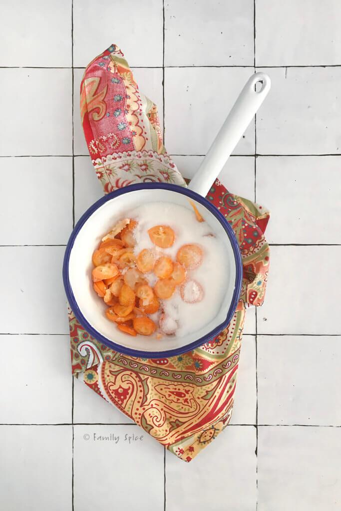 Sugar and slices of kumquat jam in a white enamel pot