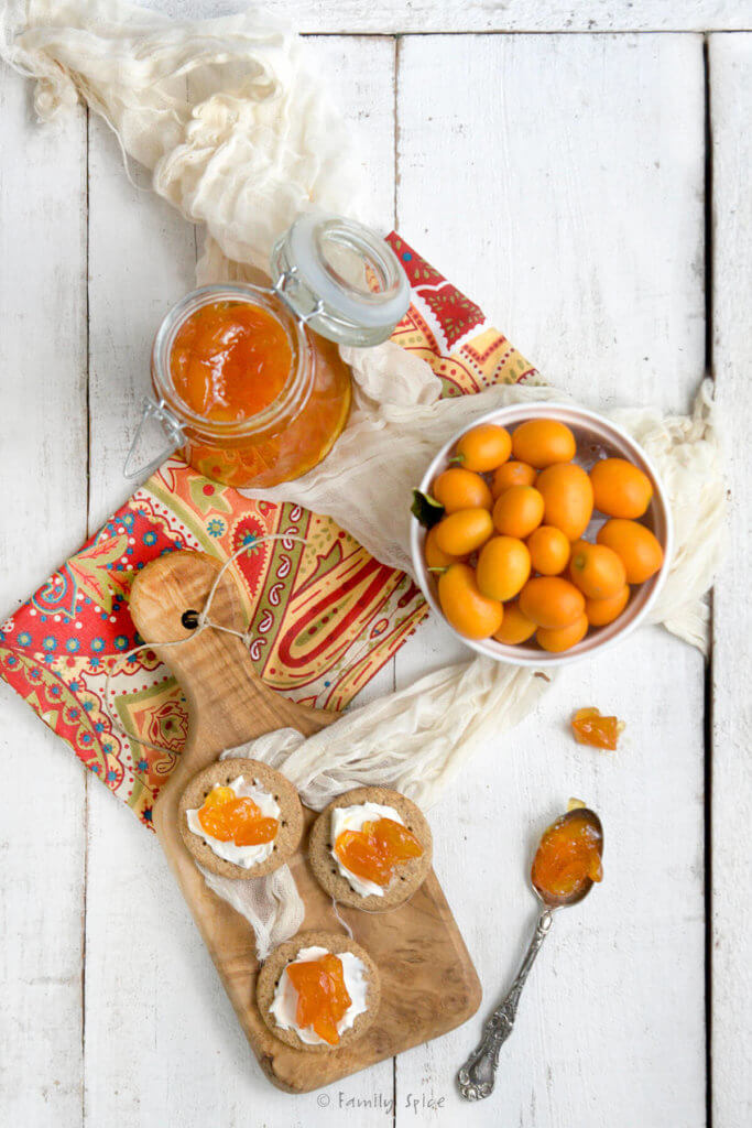 Overhead view of a cutting board with crackers topped with cheese and jam with bottle of kumquat jam and bowl of kumquats next to it