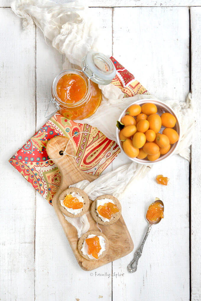 Overhead view of a bowl of kumquats, kumquat jam and cutting board with crackers covered with cheese and jam by familyspice.com