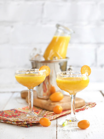 Two small stemwares with kumquat margarita with a small metal ice bucket behind it with a glass bottle of more kumquat margarita