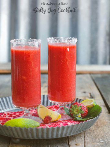 Two tall footed glasses filled with strawberry salty dog cocktail with lime wedges by FamilySpice.com