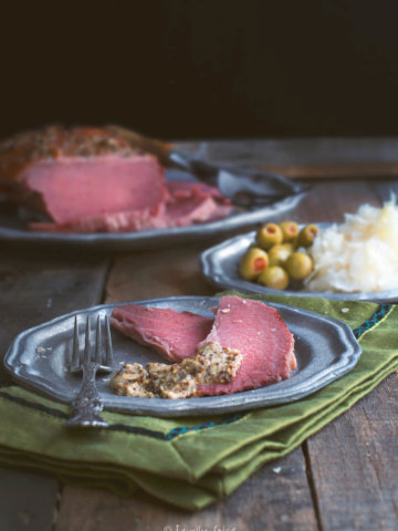 Closeup of a pewter plate with a couple slices of corned beef roast topped with grainy mustard with a whole roast behind it