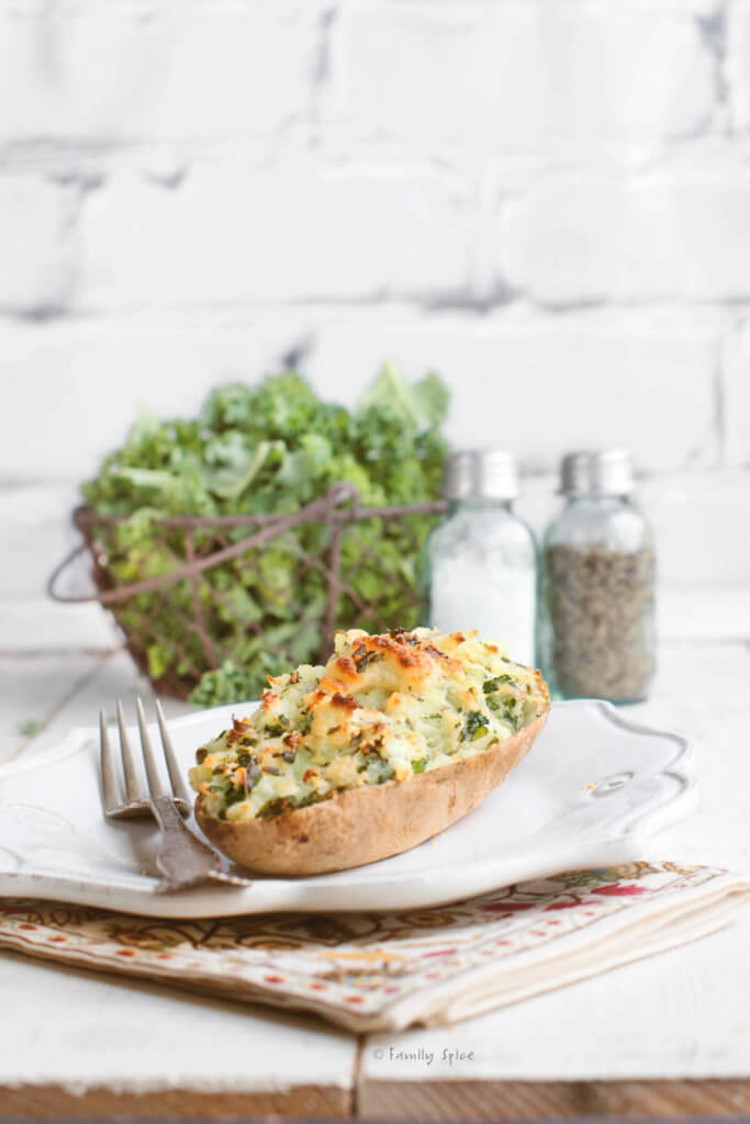 Kale twice baked potato on a white plate with a basket of kale behind it