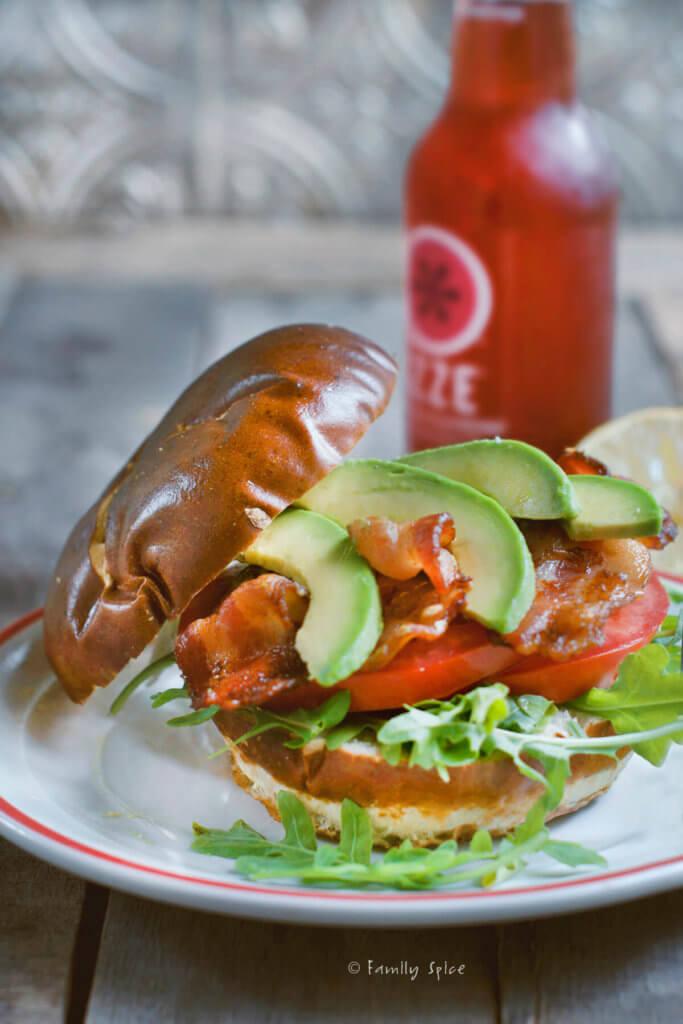 Avocado BLT sandwich on a pretzel bun with a red soda bottle behind it