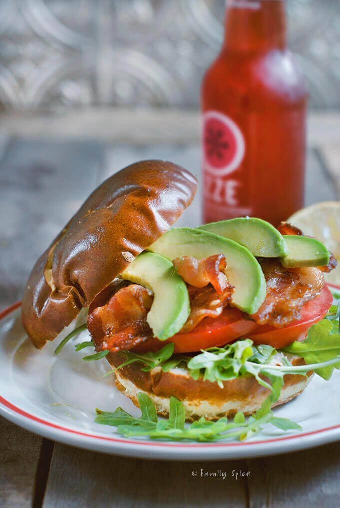 Avocado BLT sandwich with arugula and pretzel bun and strawberry soda in the background by FamilySpice.com