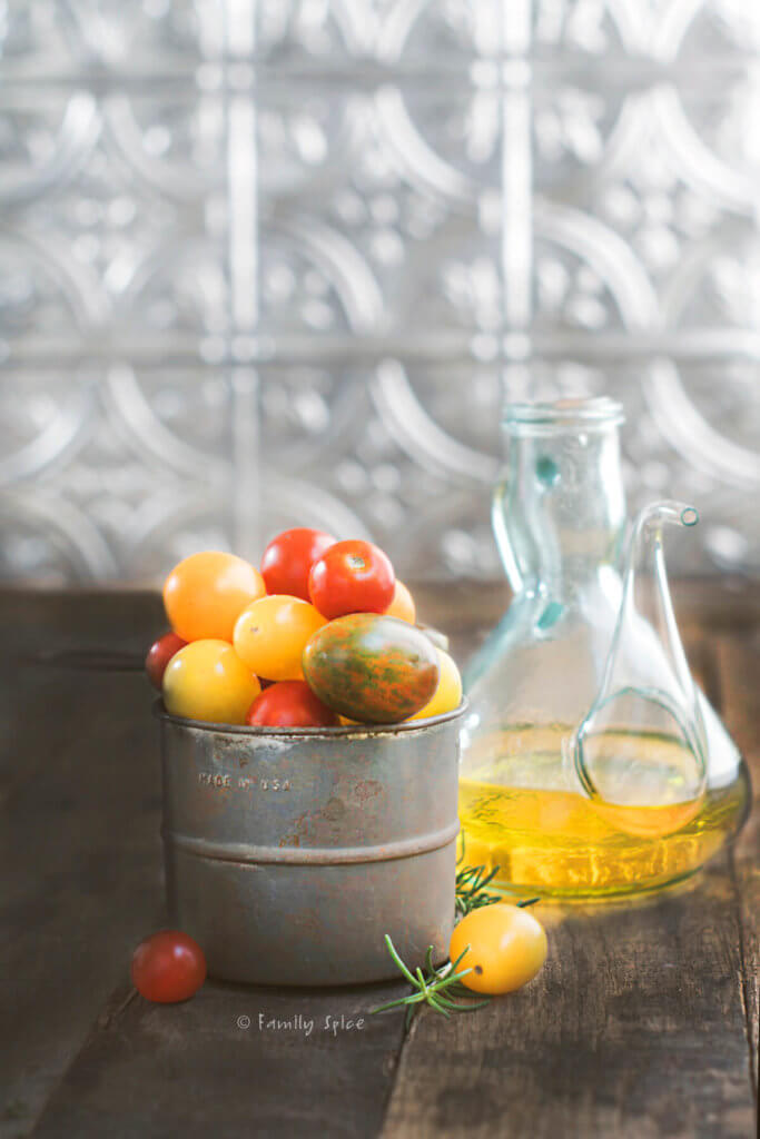 A small metal tin with cherry tomatoes next to a glass carafe of olive oil