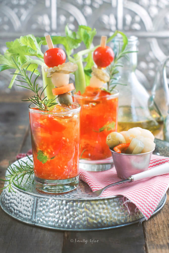 Two glasses of cherry tomato bloody marys with pickled garnishings