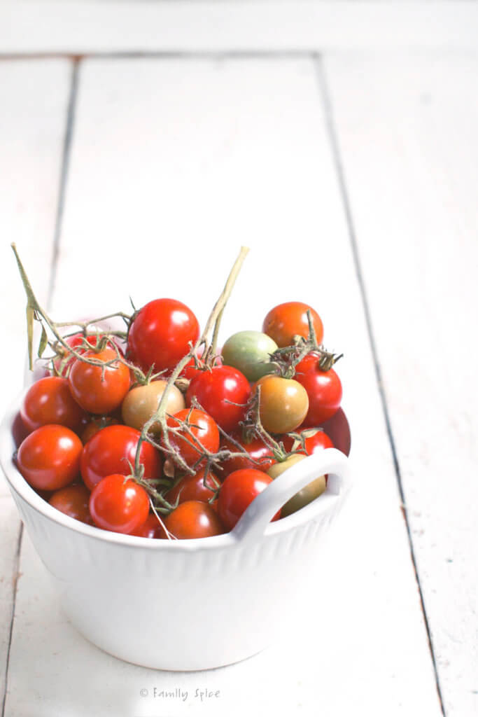 Cherry tomatoes in a white bowl on a white background