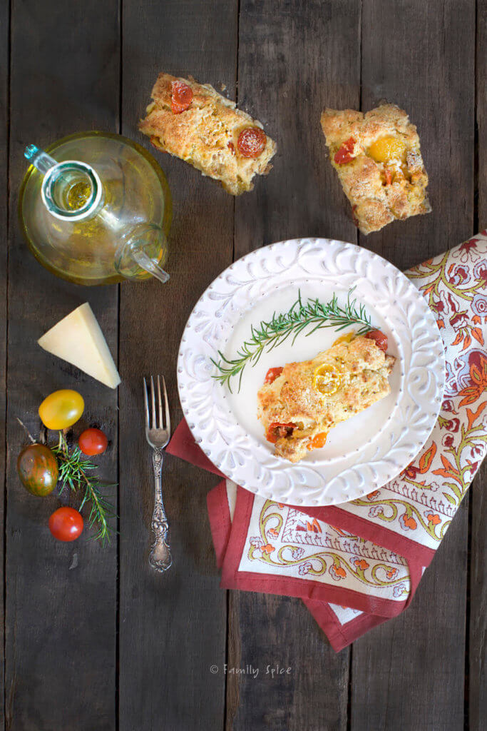 Overhead shot of a savory tomato scone on a white plate with a fork, sprigs of rosemary, more cherry tomatoes, a wedge of parmesan cheese and decanter of olive oil