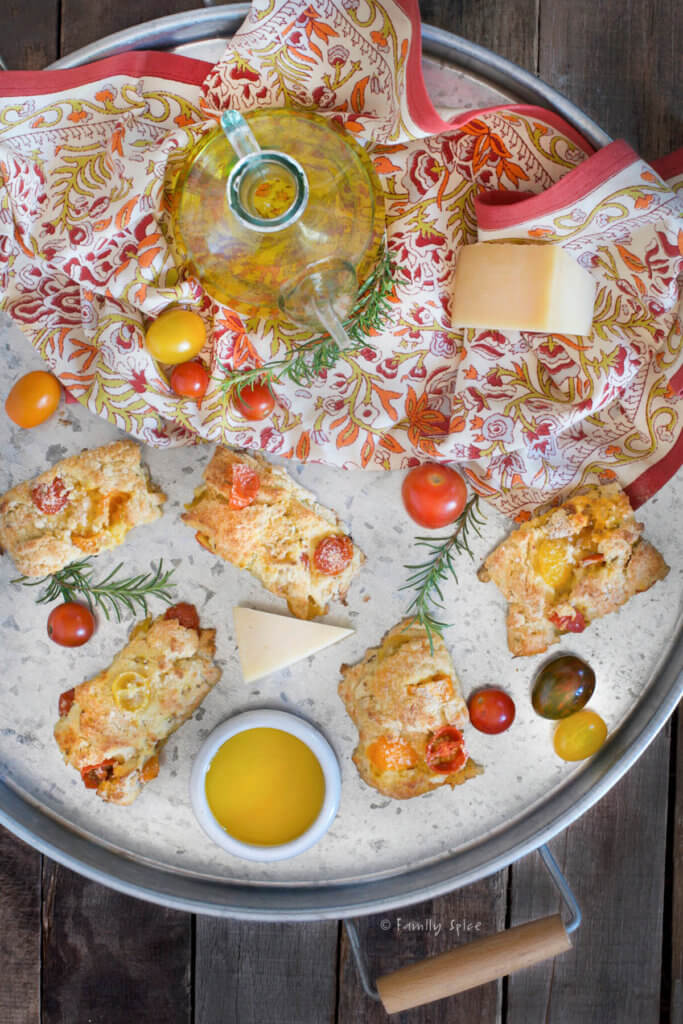 Overhead shot of a large round metal tray with savory tomato scones, an olive oil decanter, fresh cherry tomatoes and rosemary