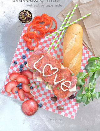 Overhead shot of an open Italian grinder submarine sandwich with olive tapenade, fresh fruit and basil by FamilySpice.com