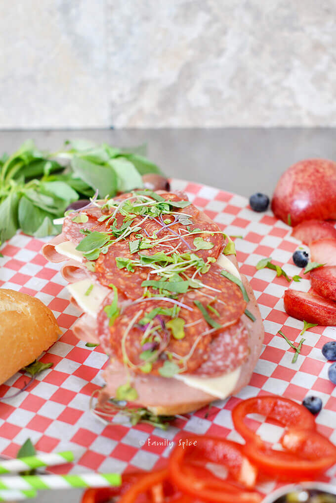 Assembling an Italian grinder submarine sandwich with olive tapenade, fresh fruit and basil by FamilySpice.com