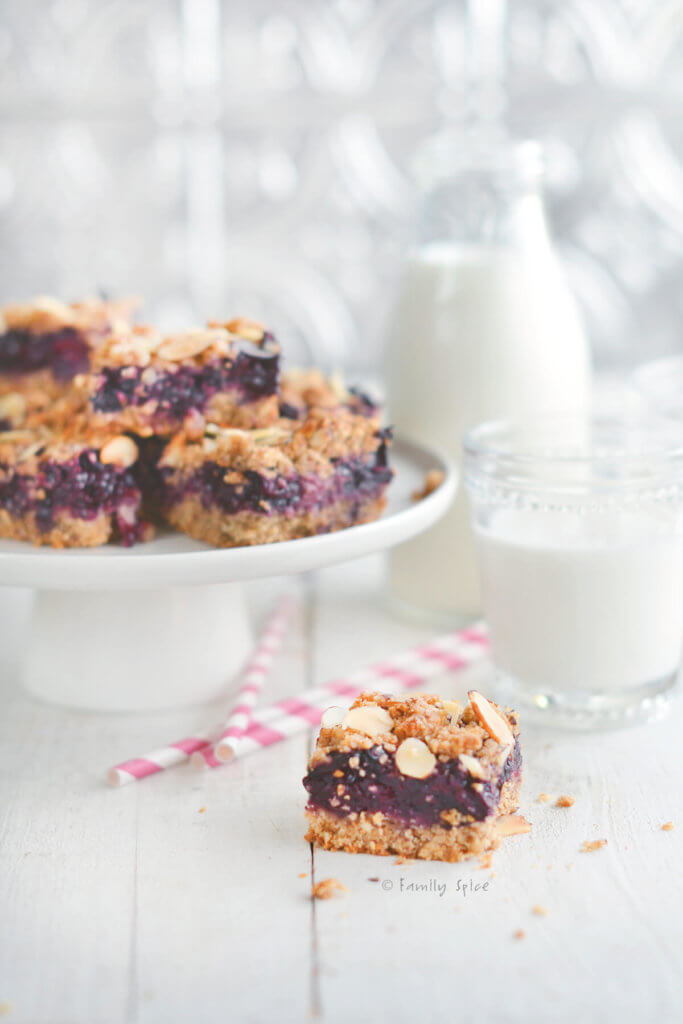 Closeup of whole wheat berry bars on a white cake stand with one bar in front and glasses of milk next to it