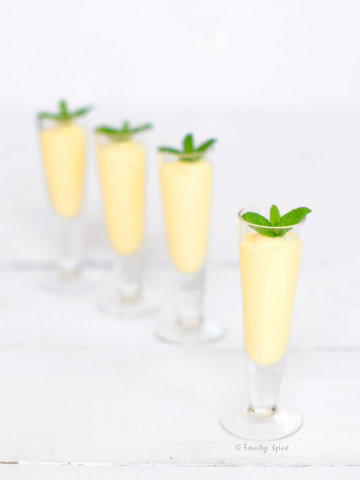 Four small shot glasses with mango rum smoothie in them and topped with fresh mint