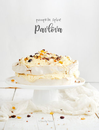 Two layer pumpkin spice pavlova stuffed with pumpkin whipped cream and topped with raisins and nuts by FamilySpice.com