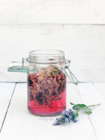 A small mason jar with sage blossom infused vinegar in it and sage blossom next to it