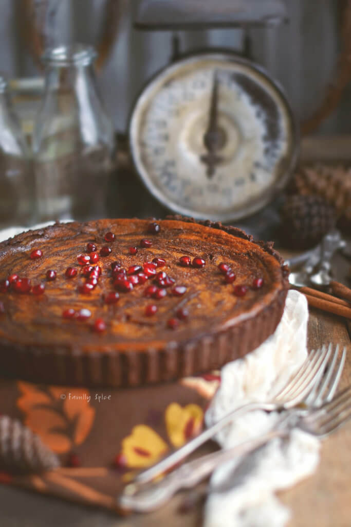 Close up of a pumpkin pie with chocolate swirls baked in a chocolate pie shell topped with pomegranate arils with an antique scale in the background