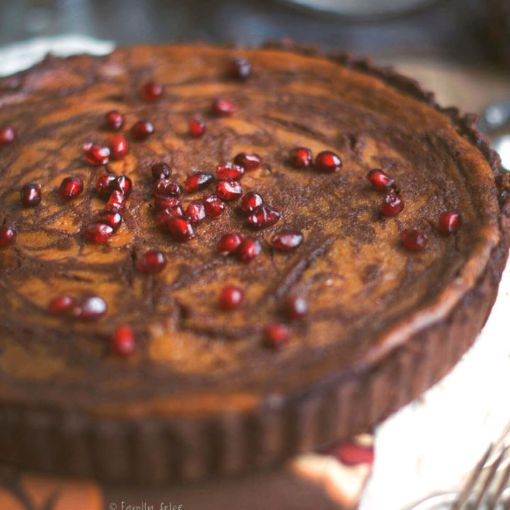 Top view of a pumpkin pie with chocolate swirls baked in a chocolate pie shell topped with pomegranate arils