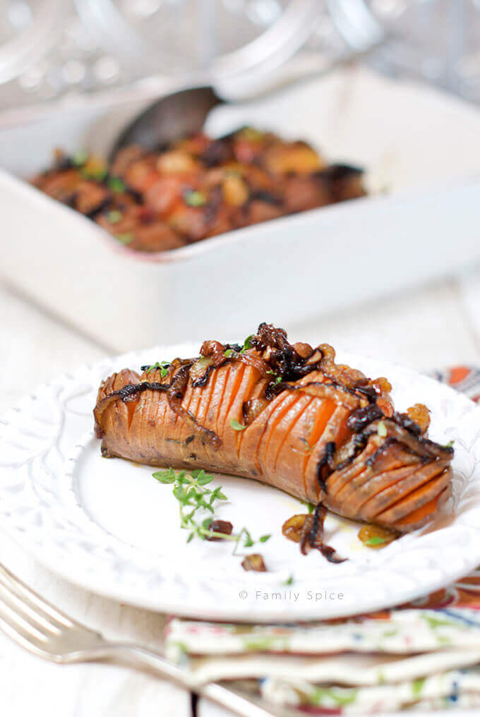 Closeup of a plate with a Hasselback Sweet Potato topped with Caramelized Onions, Pecans and Raisins by FamilySpice.com