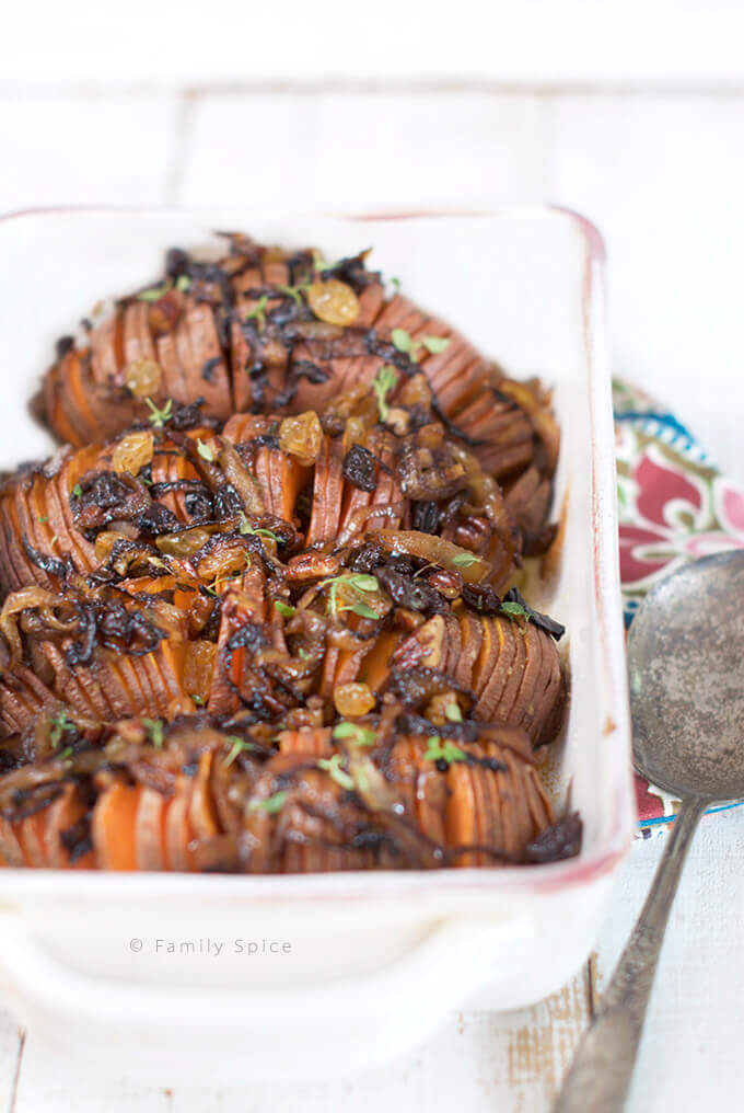 Closeup of a casserole dish filled with Hasselback Sweet Potatoes with Caramelized Onions, Pecans and Raisins by FamilySpice.com