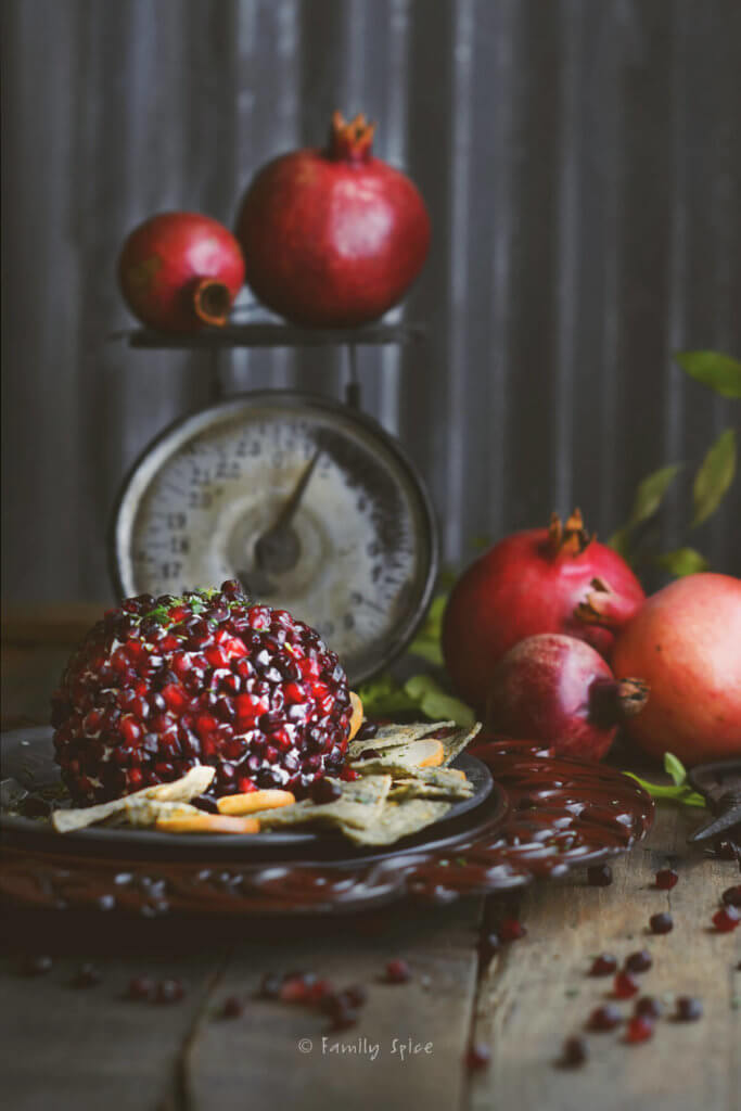 Pomegranate cheese ball with a dark rustic background with pomegranate and kitchen scale behind it