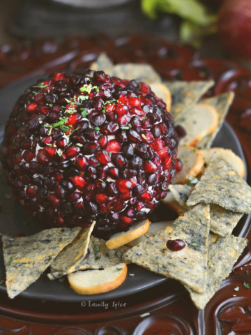 Close up of a pomegranate cheese ball with seedy chips on a rustic background