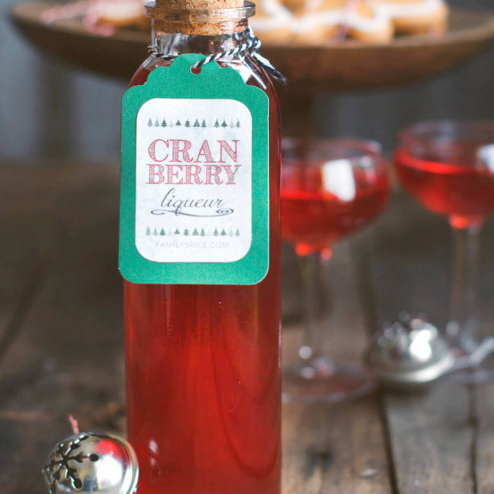 Closeup of a bottle of cranberry liqueur with two small stemmed glasses filled with it and cookies behind it