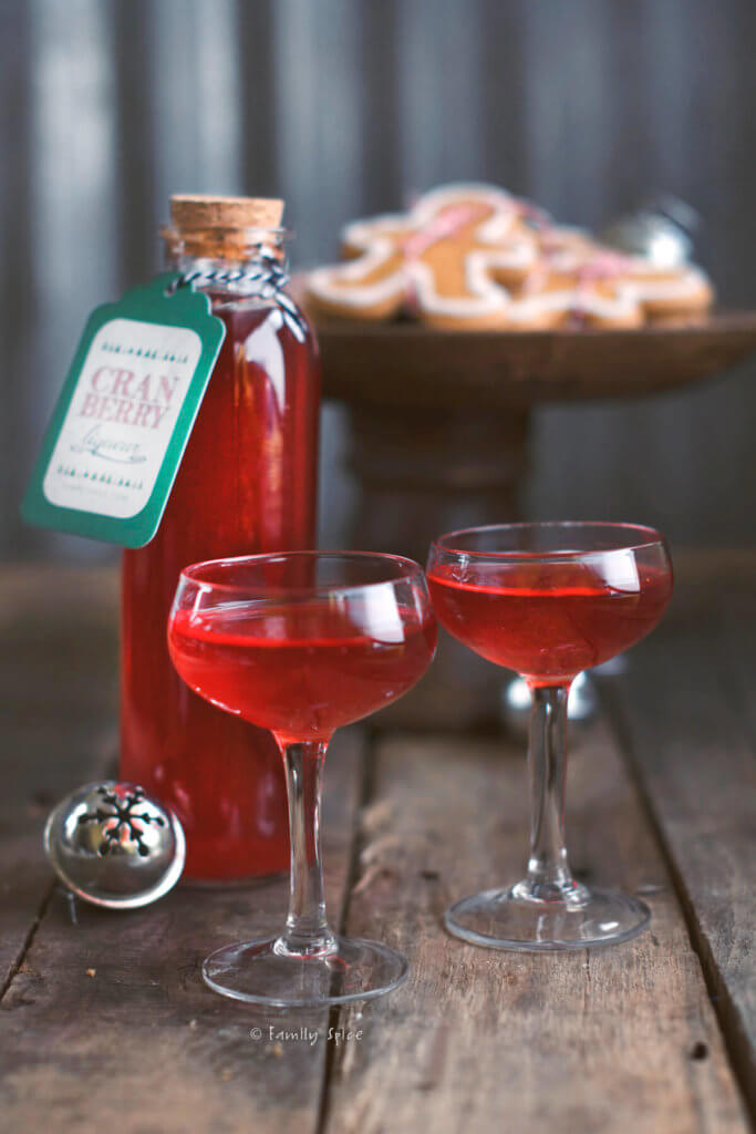 A bottle of cranberry liqueur with two small stemmed glasses filled with it and cookies behind it