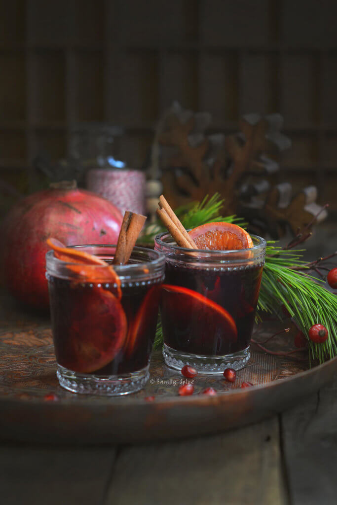 Two glasses of pomegranate mulled wine garnished with orange slices and cinnamon sticks on a dark rustic background