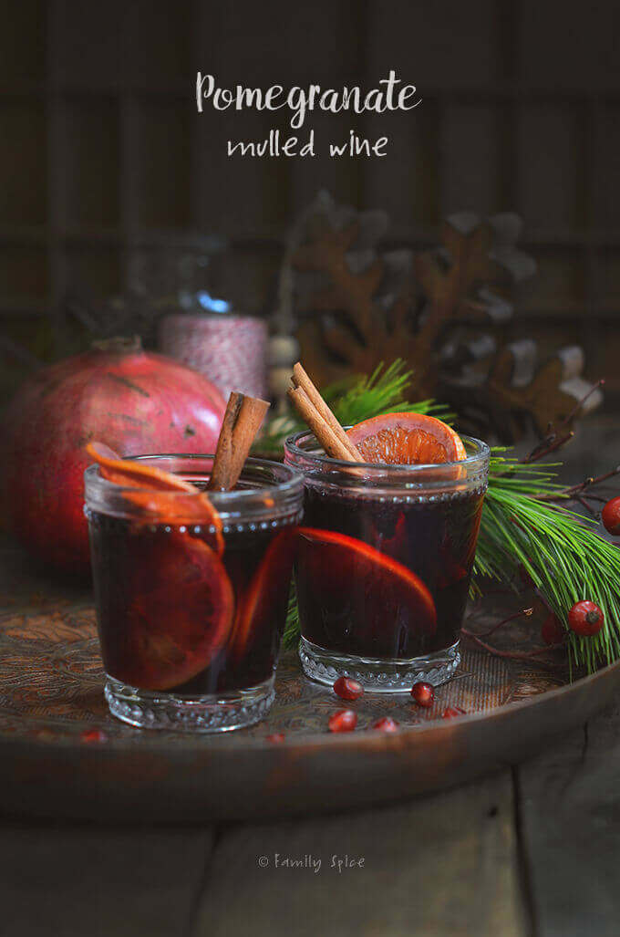 Two glasses of pomegranate mulled wine on a copper tray by FamilySpice.com