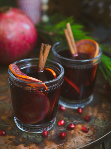Closeup of two glasses of pomegranate mulled wine garnished with orange slices and cinnamon sticks on a dark rustic background