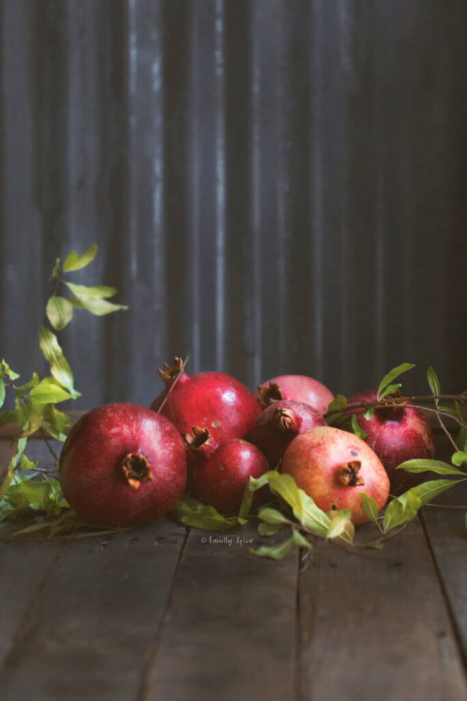 Fresh pomegranates with branches from pomegranate tree on a dark rustic bakground