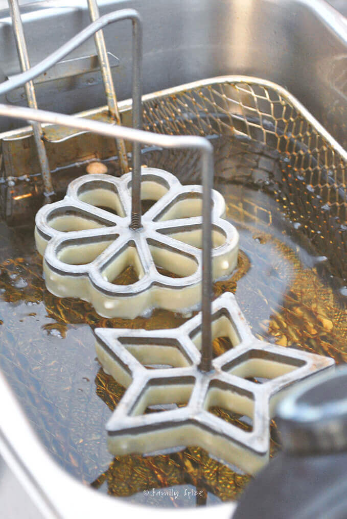 Dipping irons with batter into oil to make Persian Rosettes | Window Cookies (nan panjareh) by FamilySpice.com